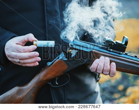 Smoke From The Trunks Of Smooth-bore Hunting Rifle After Firing. Hunter In Camouflage Takes Out Cart