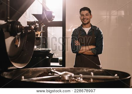 Portrait Of Smiling Coffee Roaster Standing At Roasting Machine And Looking At Camera