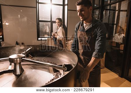 Coffee Roaster Roasting Coffee Beans In Roasting Machine With Colleague Near By