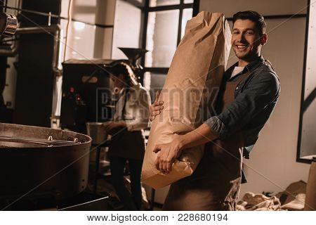 Smiling Man Holding Paper Bag With Coffee Beans With Colleague Near By In Coffee Shop