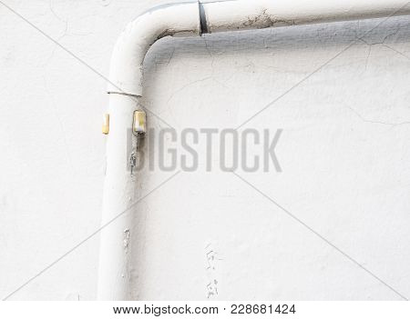White Pvc Pipe For Electrical Wire On The White Wall Of The Urban House With Copy Space.