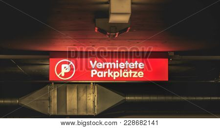 Red Illuminated Sign In A Parking Lot Where It Is Written In German Rented Parking (vermietete Parkp