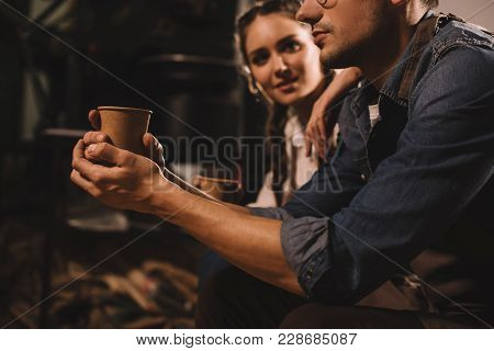 Partial View Of Couple With Cups Of Coffee Having Break During Work At Coffee Shop