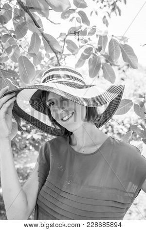 Monochrome Portrait Of A Woman In A Wide Brimmed Sunhat Standing Outdoors Looking To The Camera With