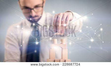Young handsome businessman using wooden building blocks with interconnected lines and dots around him