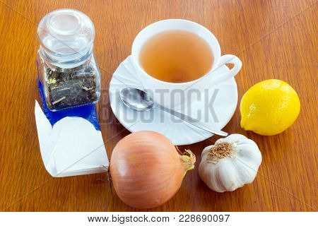 A Cup Of Tea With Saucer And Spoon, Lemon, Onion, Garlic, A Glass Dose With Tea, Paper Handkerchiefs