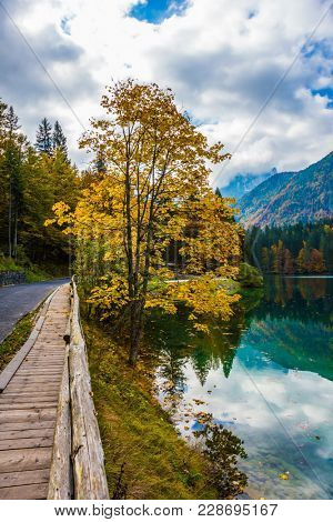 The road around the lake Lago de Fusine, is fenced with wooden handrails. The smooth surface of the water reflects the cloudy sky. Concept of cultural and ecological tourism