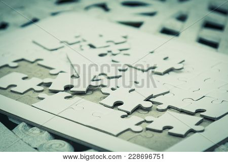 White Jig Saw Puzzle Spilled Out On The Table