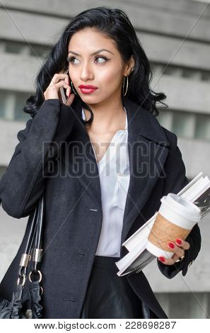 Well dressed young woman using cell phone holding coffee cup