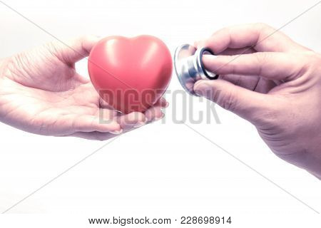 Close Up Of Man Holding Stethoscope And Checking Heart In Woman Hand; Health Care Concept On White B