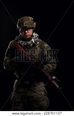Picture of military man in safety glasses with gun in his hand