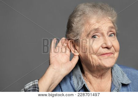 Elderly woman with hearing problem on grey background