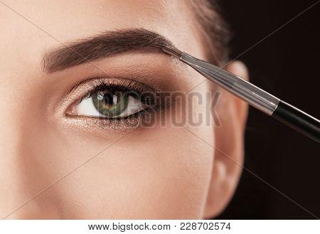 Woman applying makeup on black background. Professional visage artist work