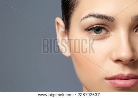 Young woman with natural eyebrows on grey background, closeup