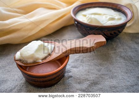 Homemade Milk Yoghurt On A Wooden Spoon Above A Clay Bowl Of Yoghurt. Organic Probiotic Greek Yogurt