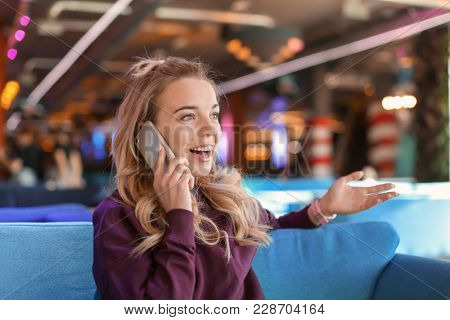Young woman in talking on mobile phone indoors