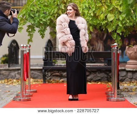 Beautiful young woman and photographer on red carpet, outdoors