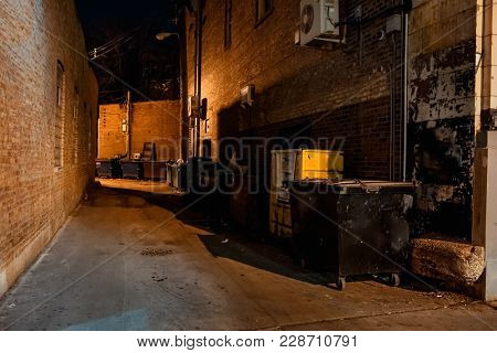 Dark empty scary urban city street alley with dumpsters and vintage buildings at night