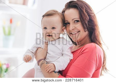 Mother and her little daughter cuddling and smiling. Parenthood concept.