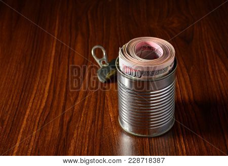 Plenty of thousand rupee Indian currency notes stuffed into metal can. A conceptual image for banned notes.