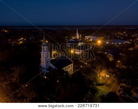 Aerial view of small town at night with church steeples.