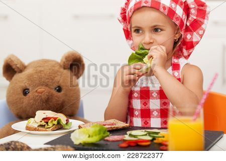 Little girl playing and having a healthy snack with her teddy bear - sitting at the table, munching at a lettuce leaf