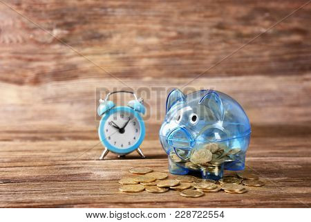 Piggy bank with coins and alarm clock on wooden table. Pension planning
