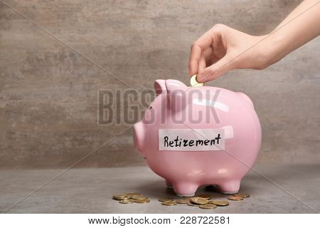 Woman putting coin into piggy bank with label