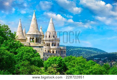 Fishermans Bastion in Budapest Hungary view to broachs from tower among crowns of green trees on background blue sky with white clouds picturesque sunny day landscape.
