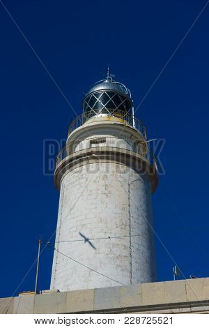 lighthouse next to the Mediterranean Sea, blue sky without clouds with calm waters. serves to warn ships of the presence of rocks