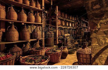 Old wine barrels, casks and bottles in wine-cellar