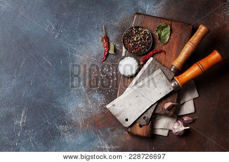 Butcher. Vintage meat knives and spices over cutting board. Top view with space for your text