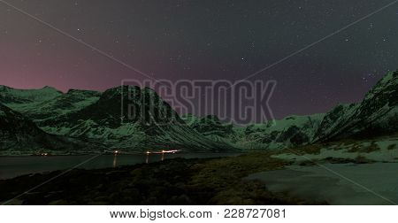 Clear Sky During A Starry Night Above The Mountains Surrounding A Norwegian Fjord Near Tromsø