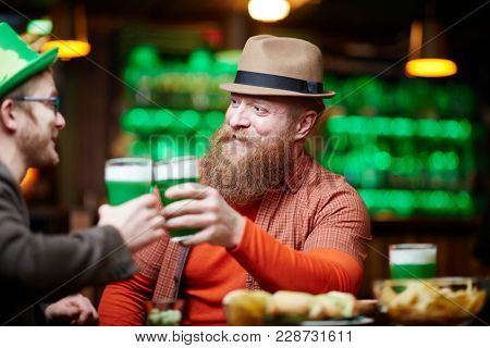 Bearded man in hat and his companion toasting with green beer while relaxing in pub