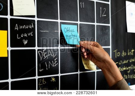Closeup of hand pulling sticky note