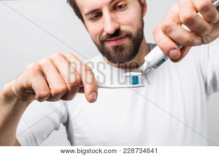 Cut View Of A Man Putting Some Tooth Paste On A Tooth Brush. He Wants To Clean His Teeth. Guy Looks