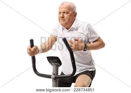 Mature man working out on an exercise bike and having a heart attack isolated on white background