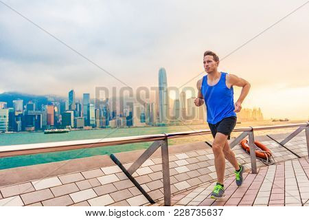 Running man runner in Hong Kong city urban skyline. Caucasian athlete training cardio jogging on the promenade of Victoria Harbor in HongKong, China, in afternoon sunset during summer. poster