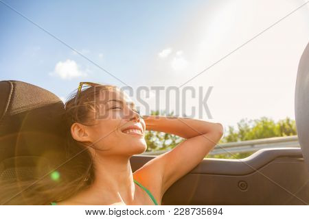 Happy girl relaxing enjoying sunshine sitting in convertible car on summer road trip vacation driving away on travel. Freedom concept woman feeling free sleeping stress free.