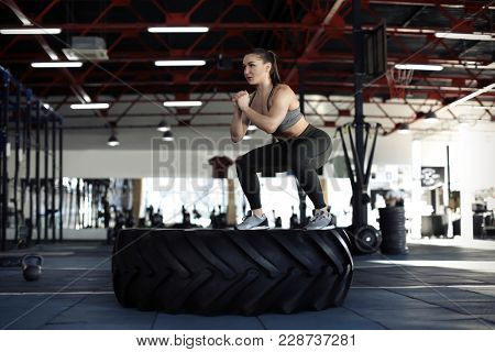 Young muscular woman training on heavy tire in gym