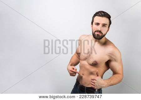 Good-looking And Awesome Guy Is Standing Of A Wall And Pointing On Himself And How His Body Is Good.
