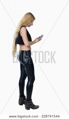 back view of standing young beautiful  girl with tablet computer in the hands of. girl  watching.   backside view of person.  Isolated over white background. Blonde in leather trousers looks at the ph
