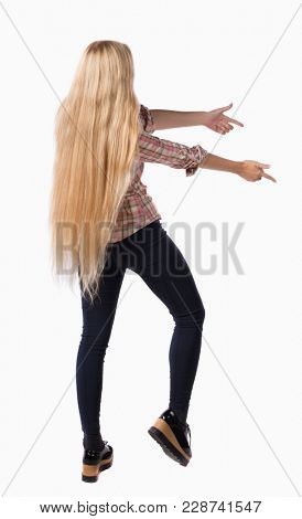 Back view of  pointing woman. beautiful girl. Rear view people collection.  backside view of person.  Isolated over white background. Girl with very long hair showing thumbs sideways.