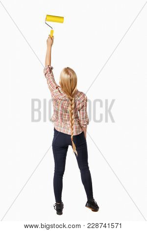 Back view of a girl who paints the paint roller. rear view people collection. backside view of person. Isolated over white background. Blonde girl in a checkered shirt paints the wall.