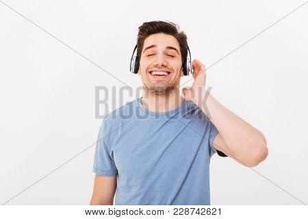 Photo of adult smiling guy having short dark hair enjoying music via earphones with closed eyes isolated over white background