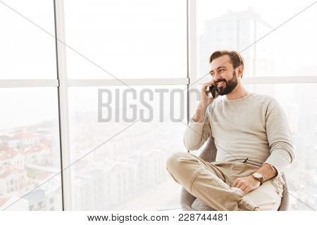 Sociable guy with beard and mustache looking through big window while sitting on modern chair and having pleasant mobile conversation in flat