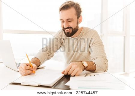 Photo of successful mature man 30s in casual clothing smiling and writing down notes on paper document while working in room with window