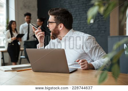Image of screaming displeased young caucasian businessman sitting indoors using laptop computer. Looking aside talking by mobile phone.