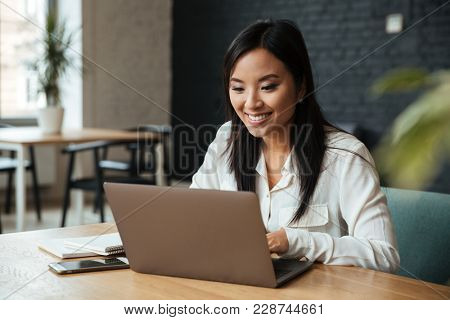 Image of happy young asian business woman sitting indoors using laptop computer. Looking aside.