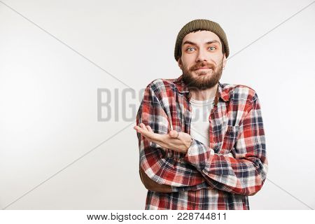 Portrait of a smiling bearded man in plaid shirt pointing away at copy space isolated over white background